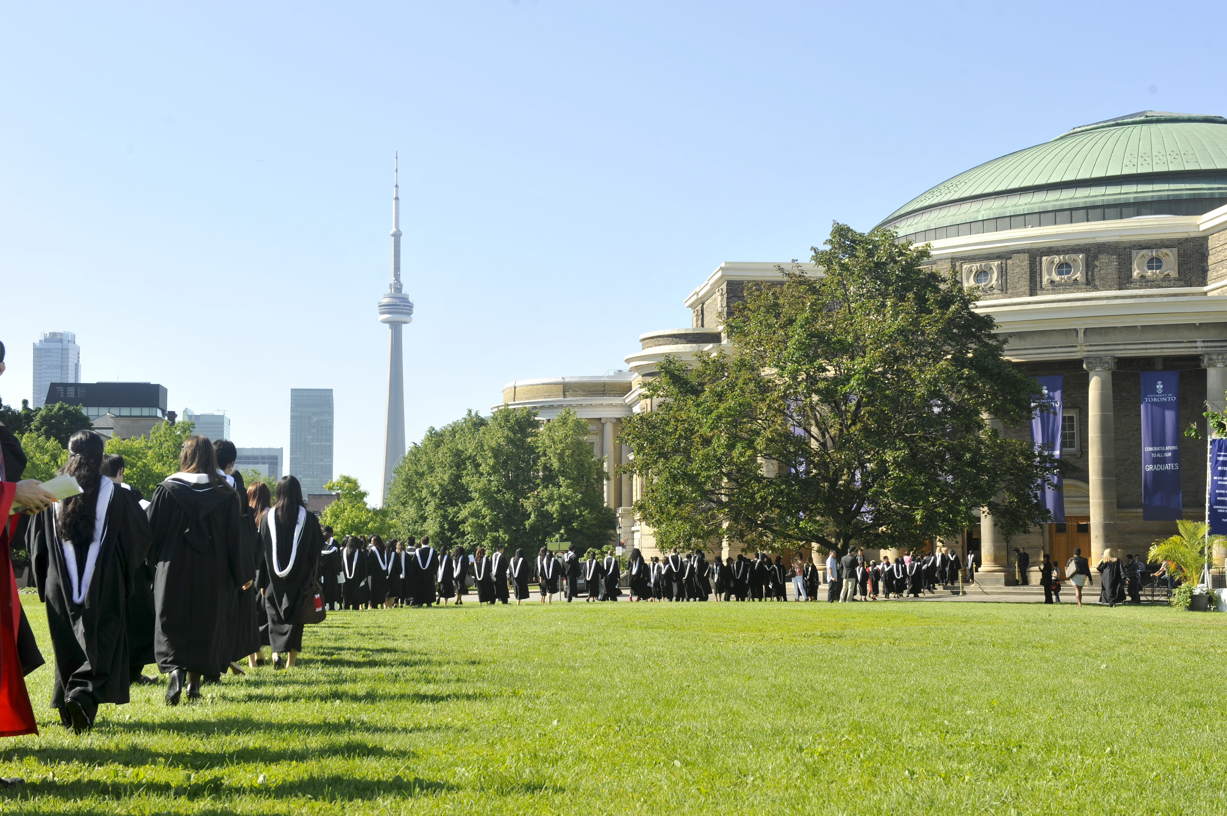 This is a picture of UofT's convocation hall, with the CN tower in the background, and the King's Circle Field in view